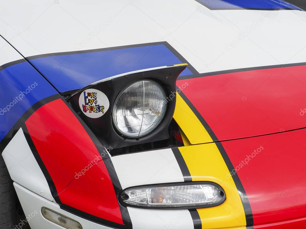 Documentary editorial image. ELBEUF, FRANCE, June 10, 2018. A Mazda MX5 painted with the colors of Mondrian painter. Close-up on the car.