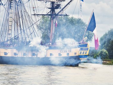 Hermione french sailboat on Seine just arriving for Armada 2019 in France, with firecracker and smoke