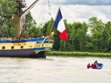 Stern close up of Hermione sailboat with french flag on Seine just arriving for Armada 2019 in France