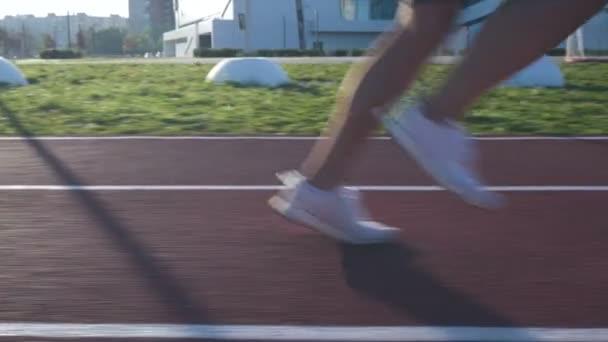 Sportoló fut a pályán futás napkeltekor.