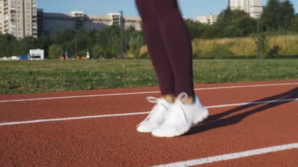 Mädchen in Sportbekleidung beim Stretching auf dem Boden sitzend.