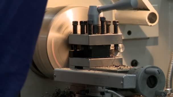 Man working at lathe metal machine rearview