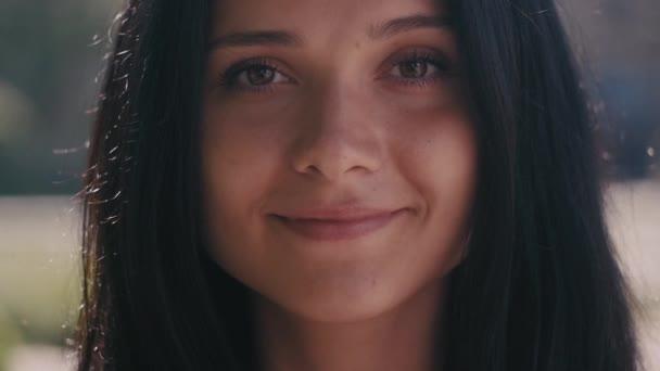 Közelről néz a kamerába, és mosolyog a város utcai elmosódott háttér gyönyörű fiatal nő barna portréja.