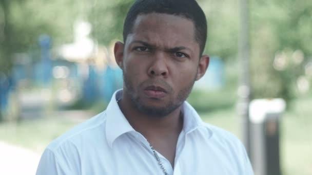 podobizna vztek mladé afroamerické muže v bílé košili, při pohledu na venkovní kamery