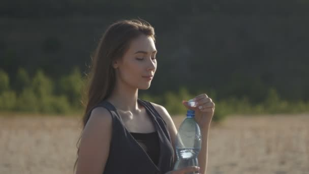 Young woman traveler drinking water from a plastic bottle in nature at hot sandy field. Girl feeling thirst with water break at sunset