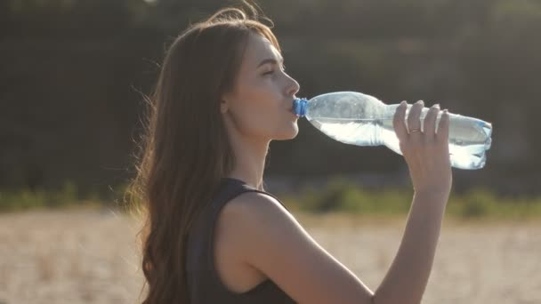young woman who is thirsty on a hot summer day drinks water from a plastic bottle