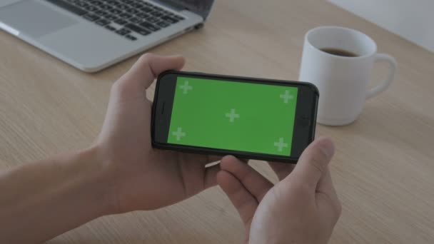 Close-up of male holds in hands smartphone with Green screen Chroma Key at workplace table, coffee and laptop on background