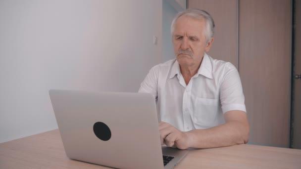 Grauhaarigen älteren Mann mit Schnurrbart arbeiten am Laptop im Büro sitzen am Tisch