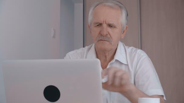 Grauhaarigen älteren Mann mit Schnurrbart arbeiten am Laptop im Büro und trinken Kaffee