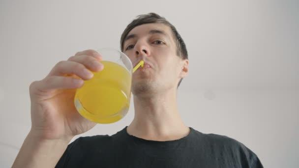 young man drinks refreshing orange soda through a tube at white background
