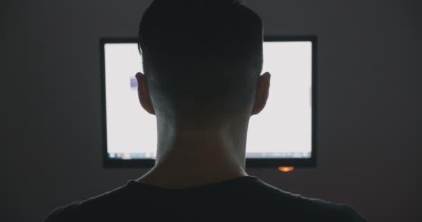 Zadní pohled na mladíka surfování internetu v noci