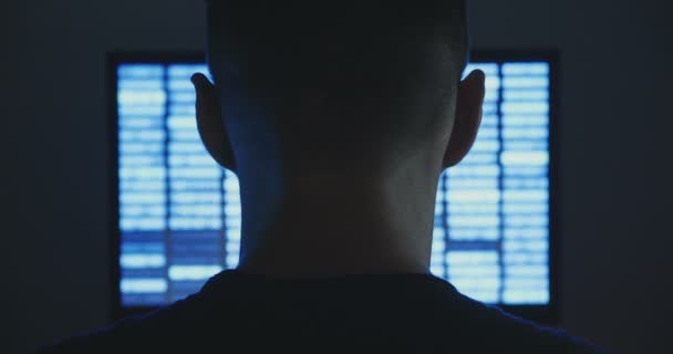 Mužské hacker funguje na počítači s binární kód na displeji v místnosti tma úřadu