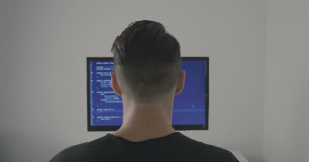 Hanno sperimentato programmatore funziona su un nuovo programma. Hacker di giovane uomo scrive il codice sorgente del software. Vista posteriore