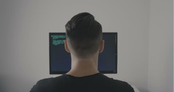 Zadní pohled hackerů programátor psaní zelené kódu při práci u počítače v kanceláři