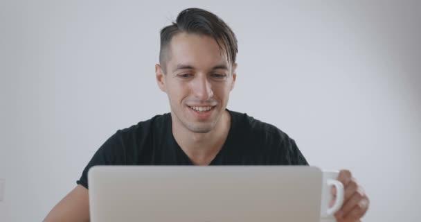 Mladý podnikatel pracuje na notebooku a pití kávy na bílém pozadí.