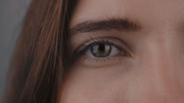 Fél arcát a fiatal Womans szem, ő néz a kamera. Fiatal womans szeme közelről