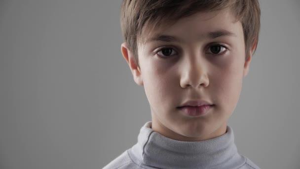 Portrét roztomilý mladých 11-12 let starý brachu při pohledu na fotoaparát na bílém pozadí