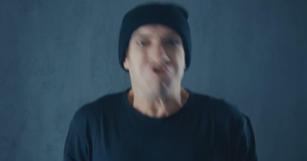 Dühös csípő férfi fekete sapka sikít agresszió portréja. Fenyegető erőszak.