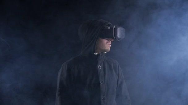 Futuristische Mann in hood Vr Kopfhörer tragen. Futuristische Mann mit Virtual-Reality-Brille in einem dunklen verrauchten Raum.