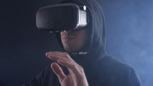 Close-up futuristischen Mann mit Kapuze trägt vr Headset. futuristischer Mann mit Virtual-Reality-Brille in einem dunklen, verrauchten Raum.