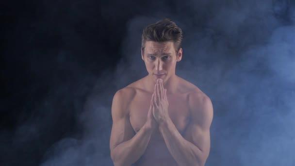 Muscular shirtless man posing on dark background, with smoke around him.