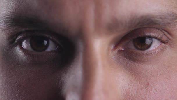 Zblízka hnědé oči mladého muže, při pohledu do objektivu fotoaparátu. Makro