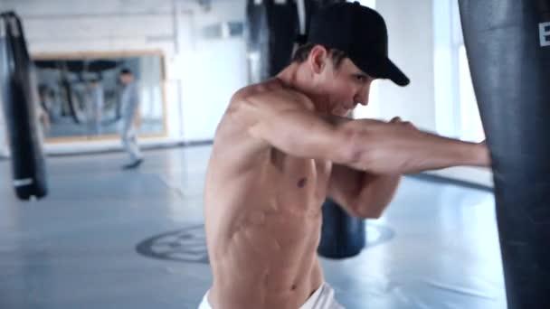 Kavkazské silák boxu v tělocvičně. Boxer sportovec trénuje s boxovací pytel