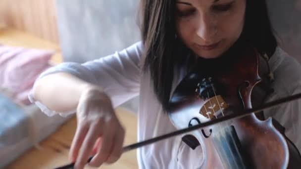 Nahaufnahme einer Musikerin im weißen Hemd, die Geige spielt