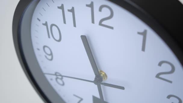 Časová prodleva velké hodiny na bílé stěně.