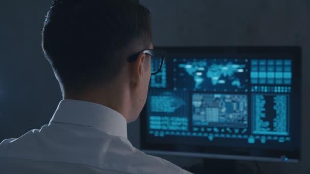 Pohled na člověka programátora v brýlích a bílé košili pracující na počítači v datovém středisku