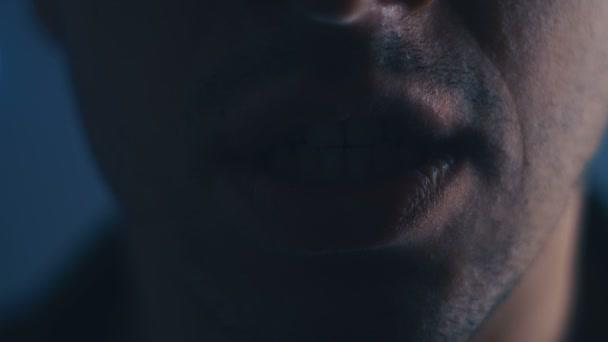 Aggressiver Mann mit wütendem Gesichtsausdruck, der im Dunkeln laut schreit. Nahaufnahme eines Mannes, der mit weit geöffnetem Mund schreit.
