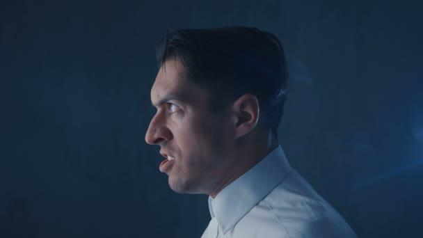 Portrait of Businessman screams on black background, anger emotions