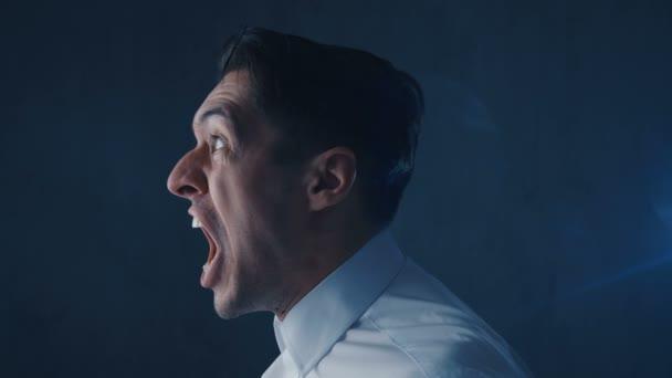 Nahaufnahme eines wütenden Geschäftsmannes, der schreit, Angst, Wut und Frustration zeigt.