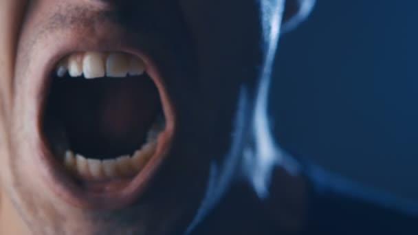 Agresszív ember dühös arckifejezés Screaming hangosan sötétben. Közelíti az ember kiabált a szája tárva-nyitva.