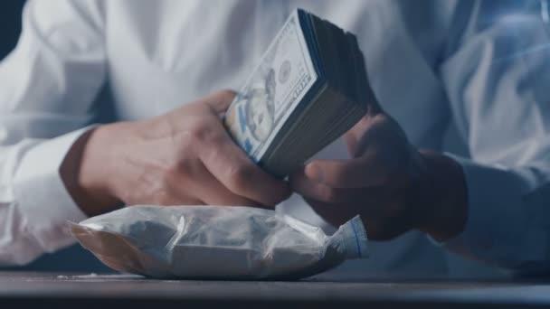 Großaufnahme eines Drogendealers mit Kokainbeutel und Pistole zählt Geld. die kriminelle Welt.