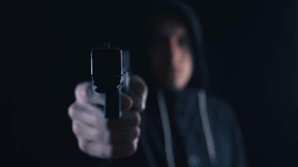 Söldner oder Attentäter mit Kapuze zielt mit Pistole auf schwarzen Hintergrund.