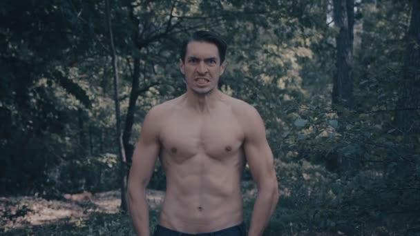 Aggressiver Mann mit nacktem Oberkörper schreit wütend im Wald