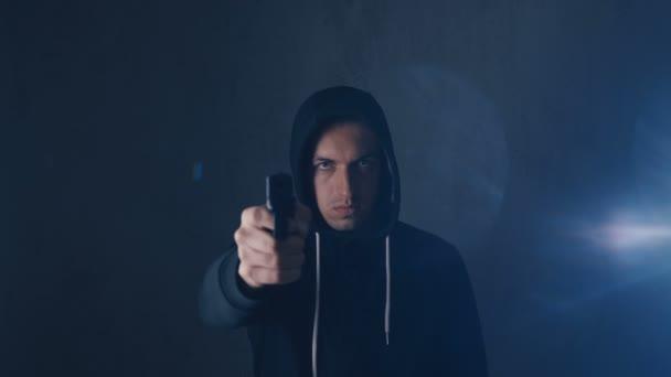 Gefährlicher Kapuzen-Verbrecher zielt mit Waffe auf schwarzen Hintergrund