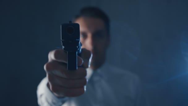 Krimineller Mann in weißem Hemd, der eine Waffe in eine Kamera richtet. Fokus auf Waffe.