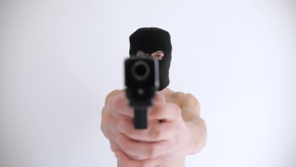 Terrorist mit nacktem Oberkörper und Sturmhaube richtet Waffe auf weißem Hintergrund