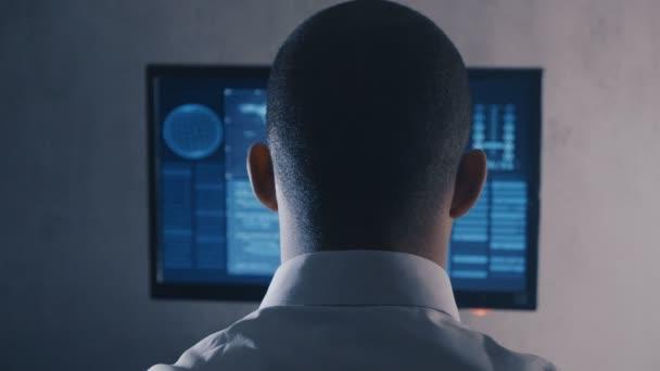 Pohled na mužského programátora v bílé košili pracující na počítači v datovém středisku