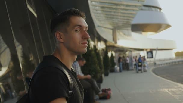 portrét mladého muže na letišti, autobusovém nebo vlakovém nádraží.