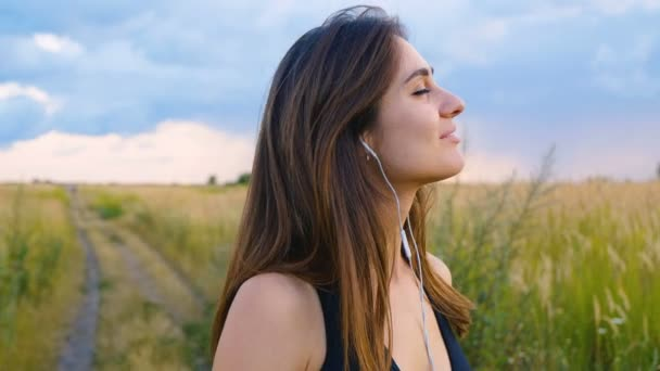 Happy young woman use smartphone and headphone standing in field at sunset, healthy lifestyle. Sportywoman runner using smartphone outdoor.