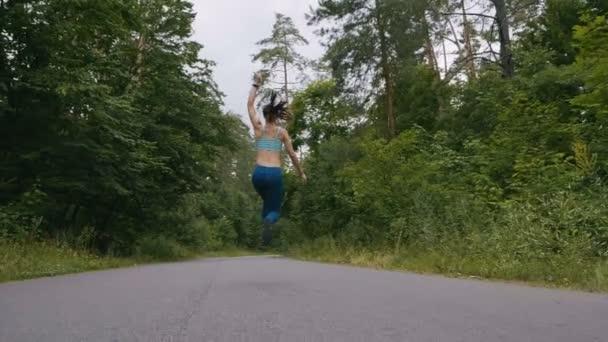 Donna corridore in esecuzione e saltare sulla strada nella foresta in slowmotion. fitness allaperto. Colpito con steadicam.