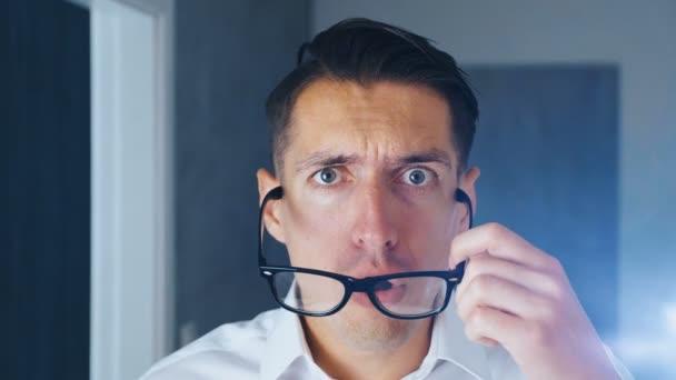 Podnikatel šokoval a zhnusený. Zmatený muž překvapeně zavdává brýle a překvapeně se dívá na kameru, zblízka.