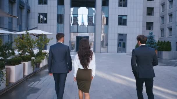 Three Successful Business People: Two handsome Men and beautiful Woman with Confident Gait Walk in the Office Building. Wearing Classical Suits. Young Confident Business Team.