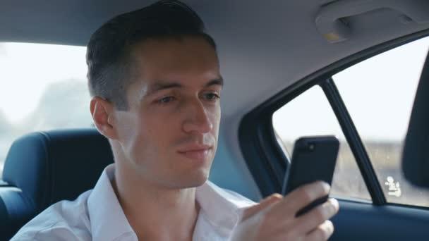 Mladý obchodník použil smartphone během cestování autem s řidičem. Člověk kontroluje mails, chats nebo New online, zatímco jezdí v taxíku.