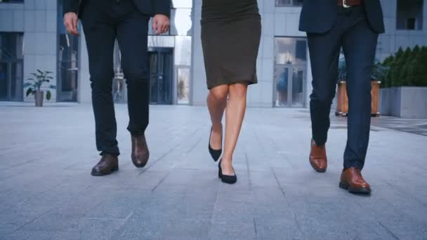 Feet of three business people commuting to work. Businessmen and businesswoman go to office building. Close up legs of Colleagues going in the city outdoor.