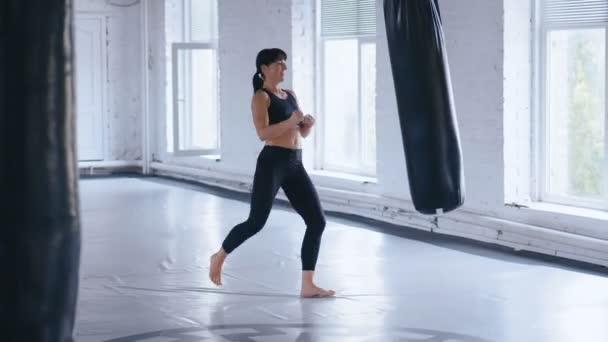 Kick-box profi sportoló nő rúgások az ütéseket táskát edzőteremben. Athletic Taekwondo nő képzés edzőteremben.