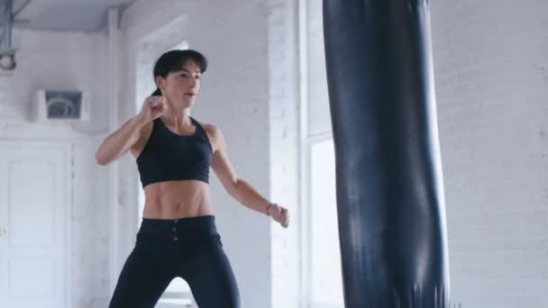 Taekwondo-Profisportlerin tritt im Fitnessstudio gegen den Boxsack. Athletische Kickboxerin trainiert im Fitnessstudio.